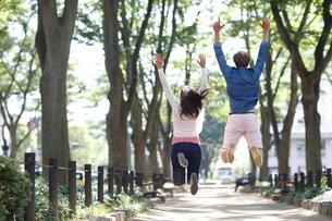ジャンプする外国人カップルの後ろ姿の写真素材 [FYI02941853]