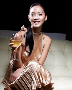 Mid-Adult Woman in Evening Dress Drinking White Wineの写真素材 [FYI02941898]