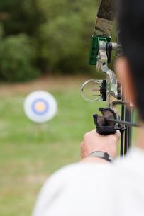 Mid adult man arrow shooting (rear view)の写真素材 [FYI02941916]