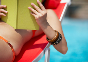 Close-Up of Mid-Adult Woman Reading Book by Poolの写真素材 [FYI02941989]