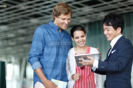 外国人カップルと旅行代理店の日本人男性スタッフの写真素材 [FYI02941993]