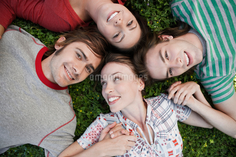 Four friends lying on grassの写真素材 [FYI02942006]