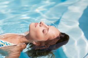 Mid-Adult Woman Floating in Swimming Poolの写真素材 [FYI02942016]