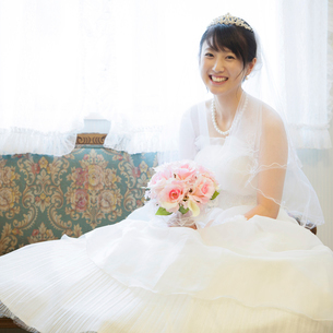 ソファーに座り微笑む花嫁の写真素材 [FYI02942096]