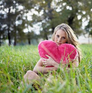 Teenager Holding Heart Shaped Cushionの写真素材 [FYI02942106]