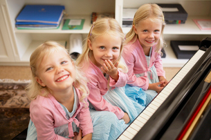 Triplets playing pianoの写真素材 [FYI02942231]