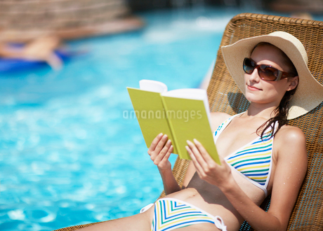 Mid-Adult Woman Reading Book on Lounge Chairの写真素材 [FYI02942237]