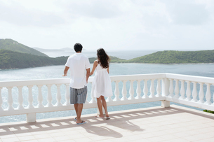 Young couple looking at ocean on balconyの写真素材 [FYI02942254]