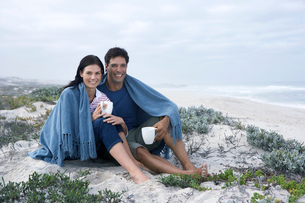 Mid adult couple drinking tea on beach,の写真素材 [FYI02942331]