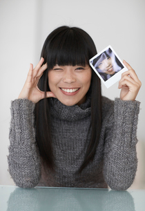 Mid-Adult Woman Holding Photograph of Herselfの写真素材 [FYI02942344]