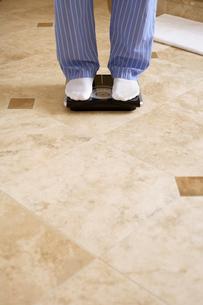 Mature man on bathroom scaleの写真素材 [FYI02942382]