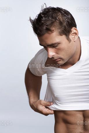 Mid adult man putting T-shirt onの写真素材 [FYI02942407]