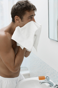 Mid adult man drying face with towelの写真素材 [FYI02942411]
