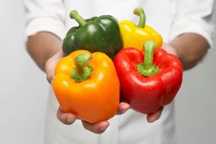Chef holding selection of bell peppersの写真素材 [FYI02942482]
