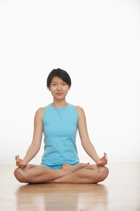 Mid Adult Woman Meditating in Lotus Positionの写真素材 [FYI02942577]
