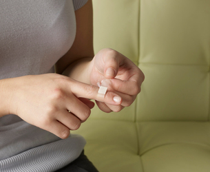 Woman Putting Plaster on Fingerの写真素材 [FYI02942587]
