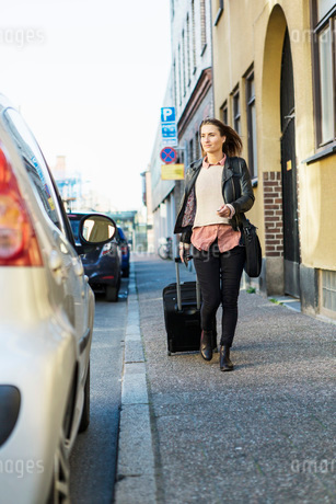 Businesswoman with luggage walking towards car parked on streetの写真素材 [FYI02942598]