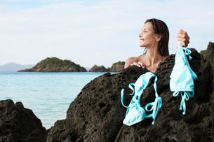 Young woman drying bikini on rockの写真素材 [FYI02942625]
