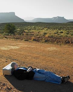 Hitchhiker sleeping at roadsideの写真素材 [FYI02942670]