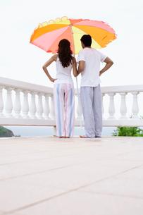 Couple standing under parasol on balconyの写真素材 [FYI02942745]