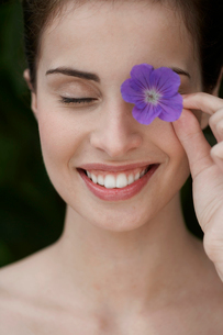 Young woman holding flower over her eyeの写真素材 [FYI02942788]