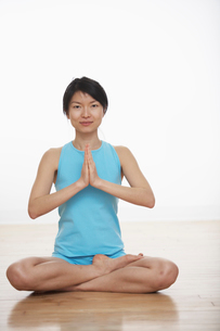 Mid Adult Woman Meditating in Lotus Positionの写真素材 [FYI02942801]