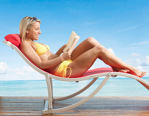 Woman Reading Book on Lounge Chairの写真素材 [FYI02942803]