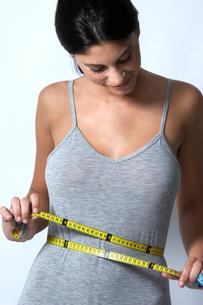 Young woman measuring waistの写真素材 [FYI02942844]