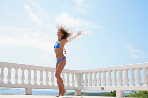 Mid adult woman jumping on balconyの写真素材 [FYI02942860]
