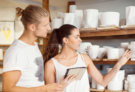 Female worker using digital tablet while discussing with male colleague at workshopの写真素材 [FYI02942866]