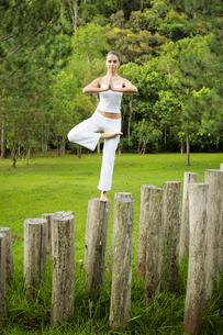 Woman doing yoga on tree stumpの写真素材 [FYI02942873]