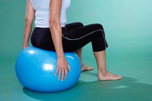 Mature woman sitting on Swiss ballの写真素材 [FYI02942901]