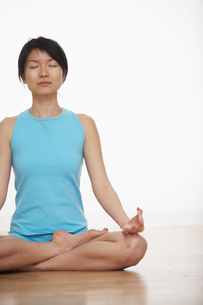 Mid Adult Woman Meditating in Lotus Positionの写真素材 [FYI02942902]