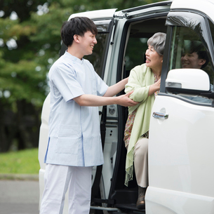 車に乗るシニア女性を支える介護士の写真素材 [FYI02942940]