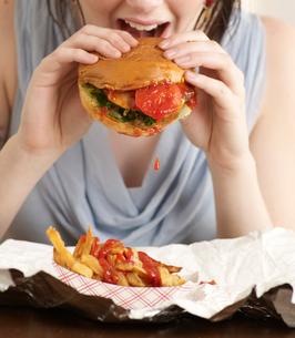 Young Woman Eating Hamburgerの写真素材 [FYI02942947]