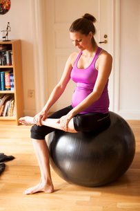 Full length of pregnant woman exercising on fitness ball at homeの写真素材 [FYI02942966]