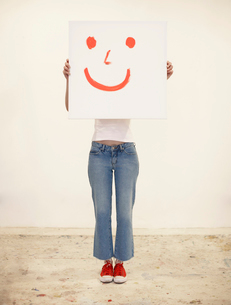 Woman holding drawing of smiley faceの写真素材 [FYI02942985]