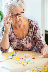Senior woman solving jigsaw puzzle at table in nursing homeの写真素材 [FYI02942986]