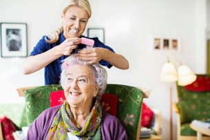 Happy female caretaker putting curlers to senior woman's hair at nursing homeの写真素材 [FYI02942995]