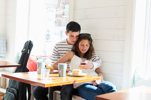 Loving couple using mobile phone at restaurantの写真素材 [FYI02943005]