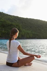 Mid adult woman meditating on beachの写真素材 [FYI02943031]