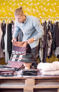 Male owner arranging cloths in clothing storeの写真素材 [FYI02943040]