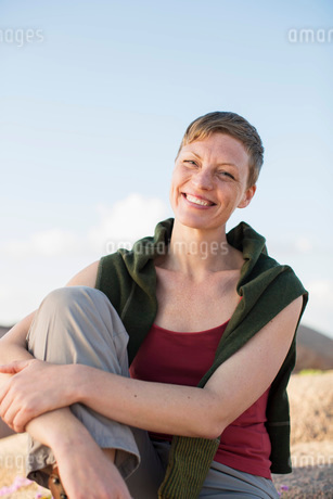 Portrait of happy woman relaxing on rock against clear skyの写真素材 [FYI02943055]