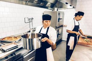 Kvinnlig kock b?r p? gryta i restaurangk?kの写真素材 [FYI02943063]
