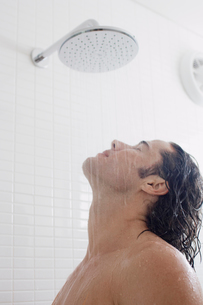 Young man taking showerの写真素材 [FYI02943077]