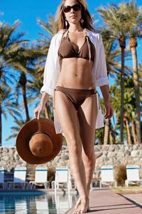 Woman in bikini walking by poolの写真素材 [FYI02943085]