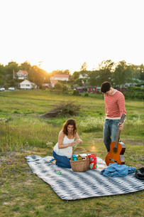 Couple preparing for picnic on fieldの写真素材 [FYI02943091]