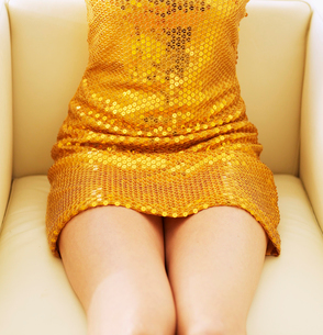 Mid-Section of Woman in Golden Dressの写真素材 [FYI02943097]