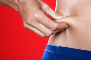 Woman pinching skin around abdominalsの写真素材 [FYI02943119]