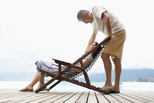 Mature couple relaxing on deckの写真素材 [FYI02943136]